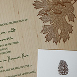 Alana and Matthew: wood veneer invitation with leaf, acorn, and pinecone motifs in moss and espresso