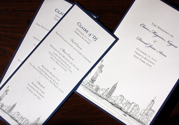 Claire and Daniel: wedding day items including program, menu and stickers featuring NYC skyline and taxicab illustrations